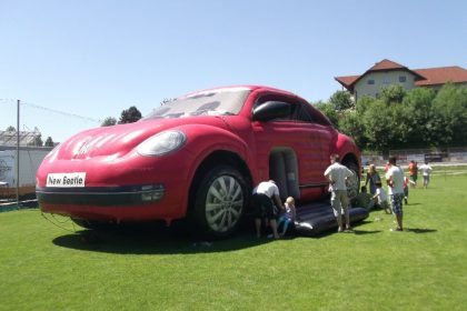 Hüpfburg VW Beetle in rot auf Wiese aufgebaut mit Kindern und Erwachsenen davor