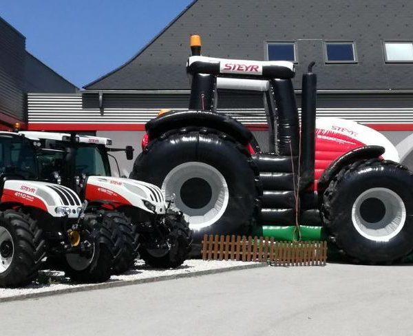 Aufblasbarer Steyr Traktor in weiß und rot neben echten fahrtüchtigen Steyr Traktoren