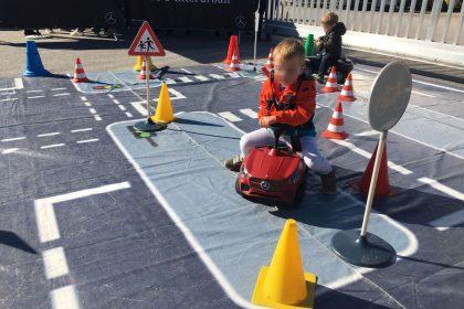 Junge auf rotem Mercedes Bobby Car fährt entlang eines aufgebauten Parcours
