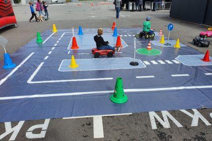 Mehrere Kinder sind auf einem aufgebauten Parcours mit Bobby Cars unterwegs