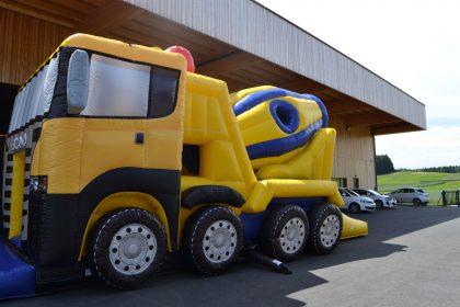 Aufblasbare Scania Betonmischwagen-Hüpfburg in gelb und blau von der Seite