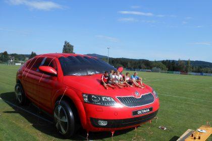 Aufblasbare Skoda Octavia Hüpfburg in rot mit Jugendlichen auf der Motorhaube