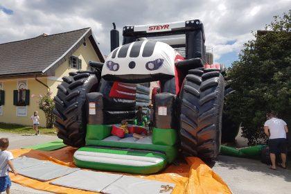 Aufblasbare Steyr Traktor Hüpfburg in weiß und rot von vorne