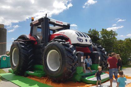 Aufblasbare Steyr Traktor Hüpfburg mit Kindern und Erwachsenen davor