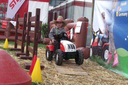 Ein Junge mit Strohhut fährt mit einem Steyr Trettraktor auf Stroh